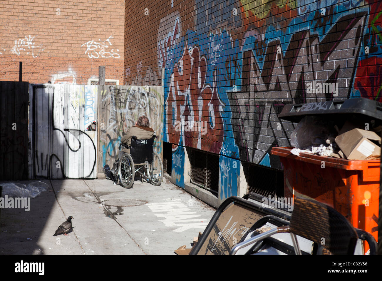 A transient staring at a wall in a back alley of St. Kilda, Melbourne, Australia. - Stock Image