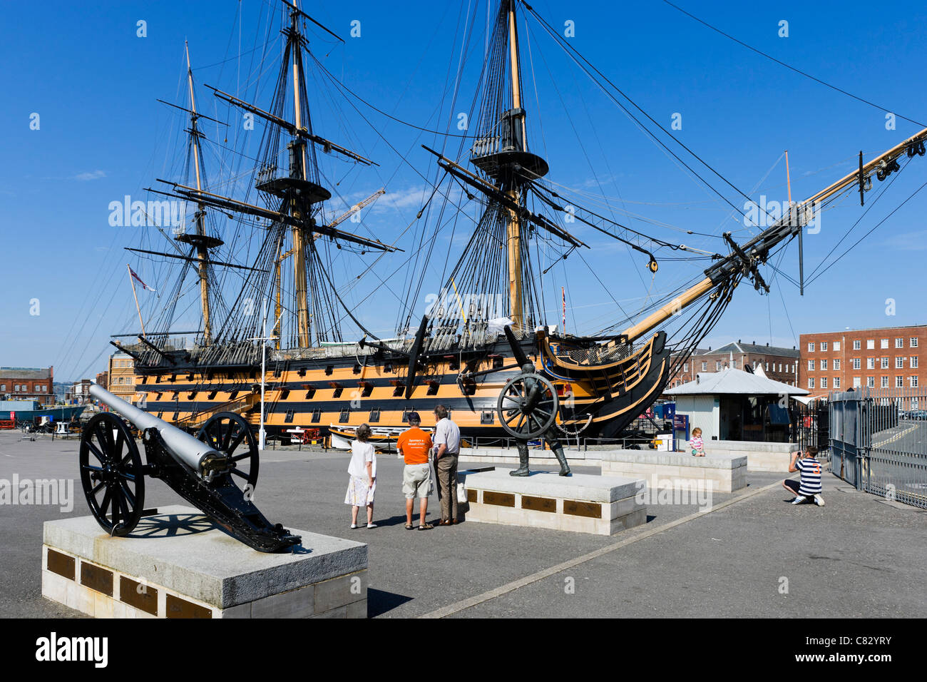 Tourists in front of Lord Nelson's flagship HMS Victory in Portsmouth Historic Dockyard, Portsmouth, Hampshire, - Stock Image