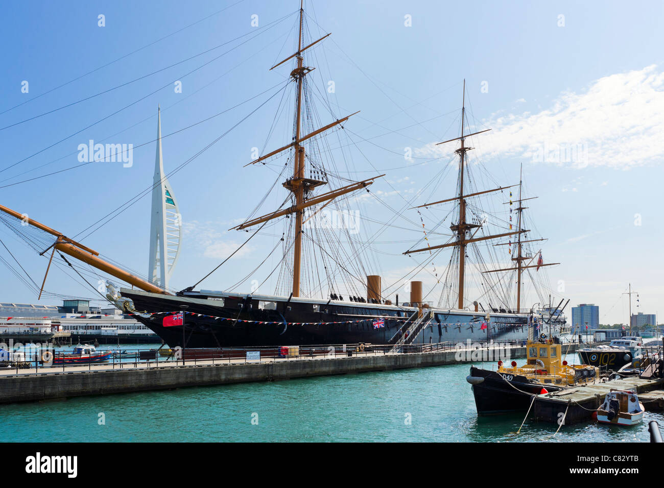 HMS Warrior ( first iron-hulled steam/sail warship from1860) with Spinnaker Tower behind, Portsmouth Historic Dockyard, - Stock Image