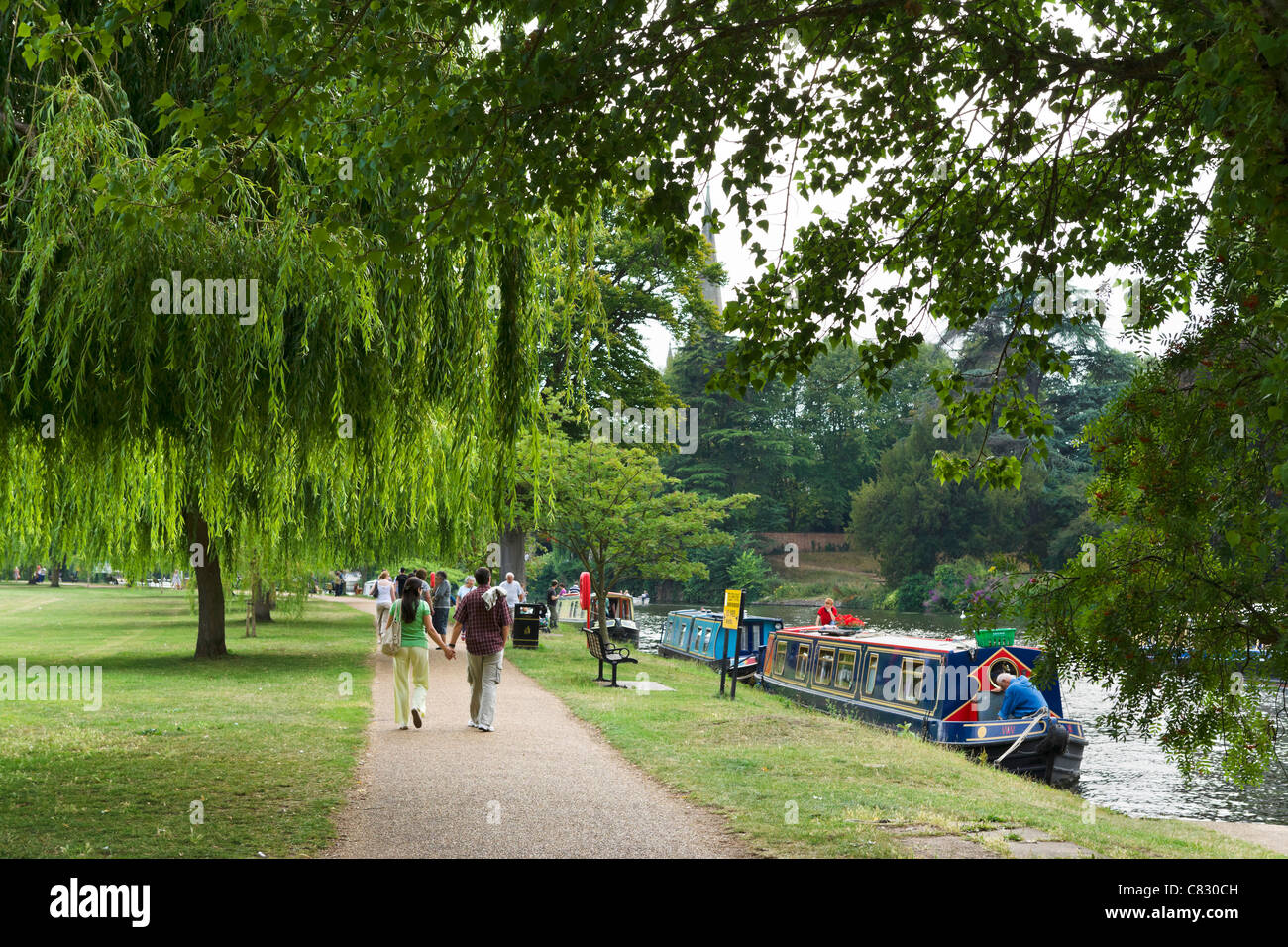 Couple walking hand in hand along the banks of the River Avon, Stratford-upon-Avon, Warwickshire, England, UK - Stock Image