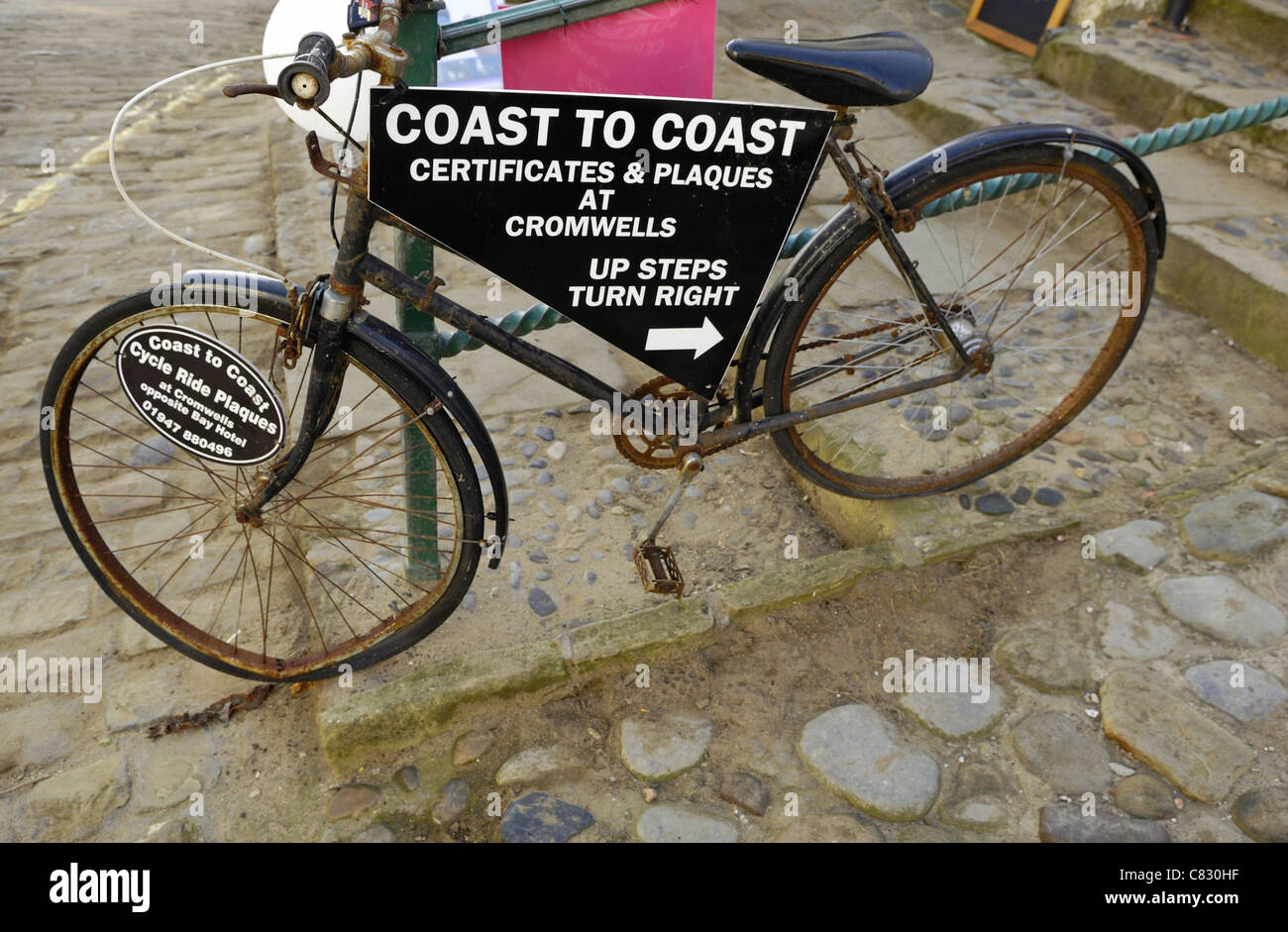 An old rusty black cycle advertising certificates for the completion of the Coast to Coast from St Bees to Robin Stock Photo