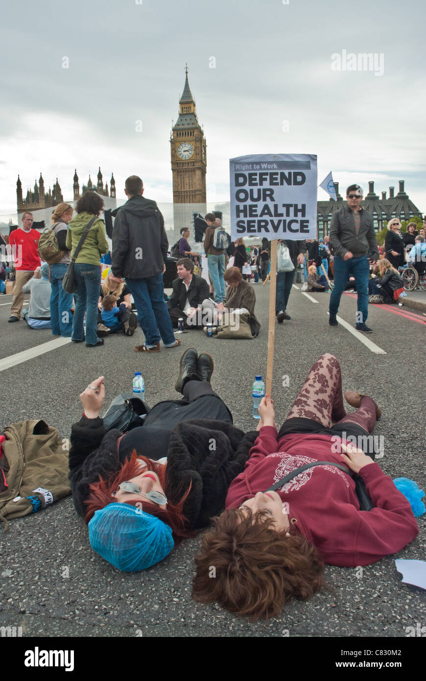 Two women lie down on Westminster Bridge with placard 'Defend our Health Service' behind is Big Ben. Health - Stock Image