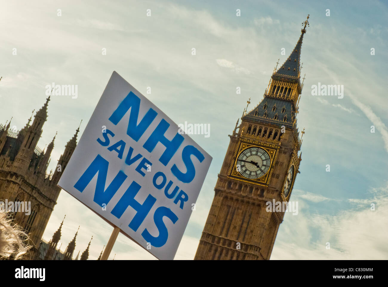 Single placard 'NHS SAVE OUR NHS' against Big Ben both at a jaunty angle. - Stock Image
