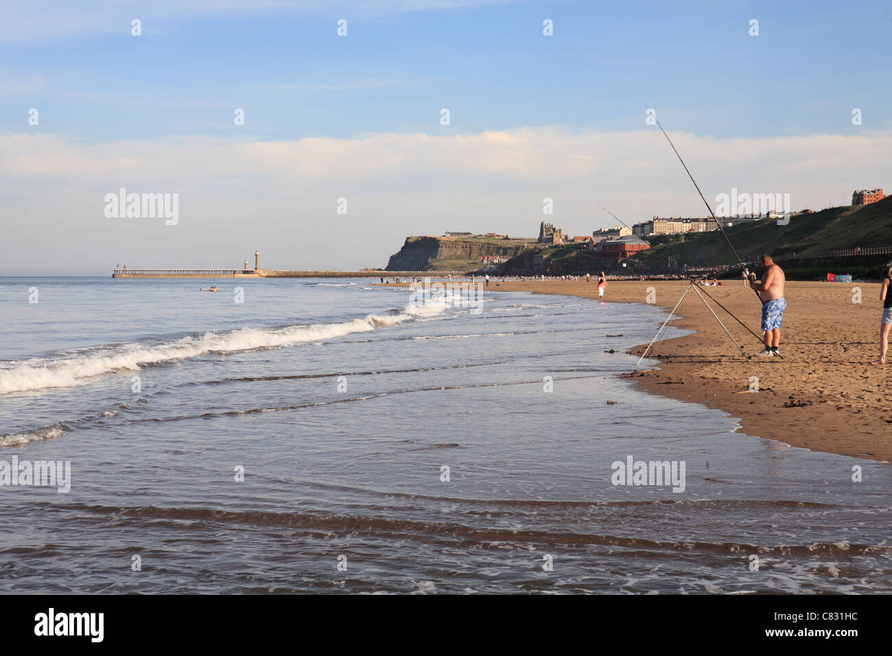 Mna fishing from the beach at Whitby, Yorkshire, England - Stock Image