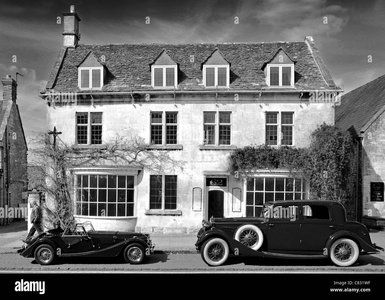 Two classic cars parked outside a historic building, Broadway, Cotswolds. Available in colour and black and white. - Stock Image