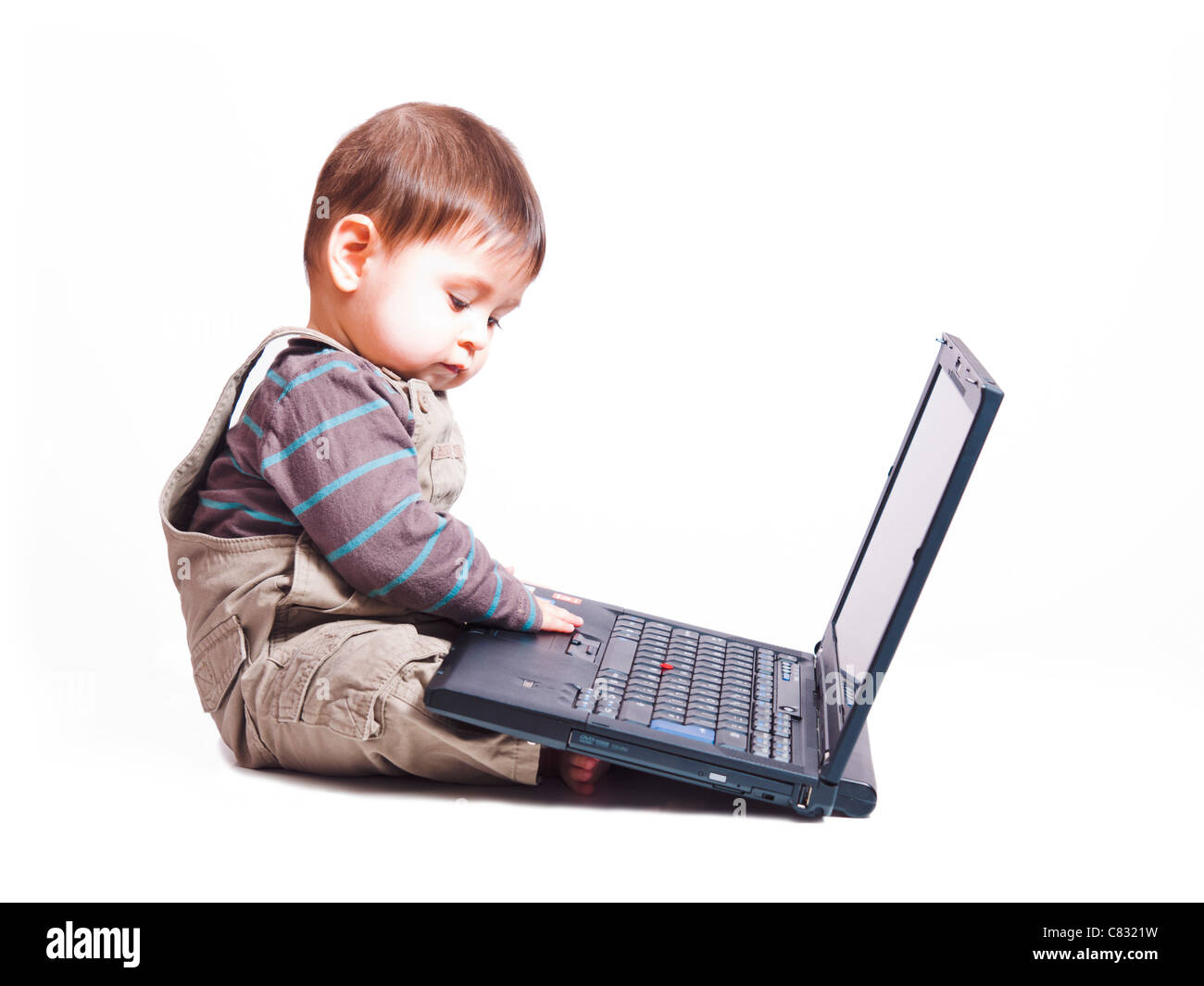 6 month baby boy sitting in front of laptop - Stock Image