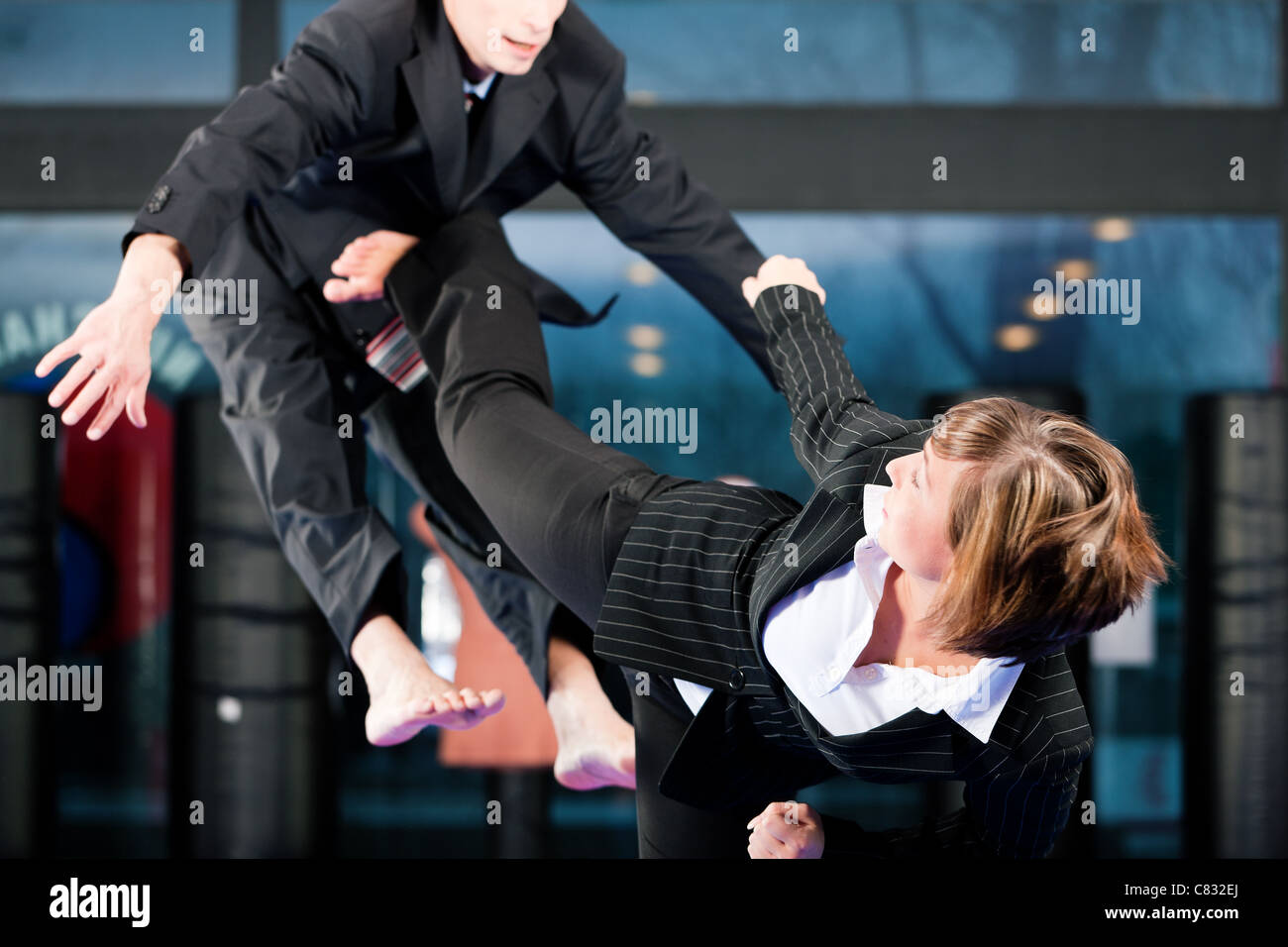 Business concept - People in a gym in martial arts training exercising Taekwondo, both wearing suits - Stock Image