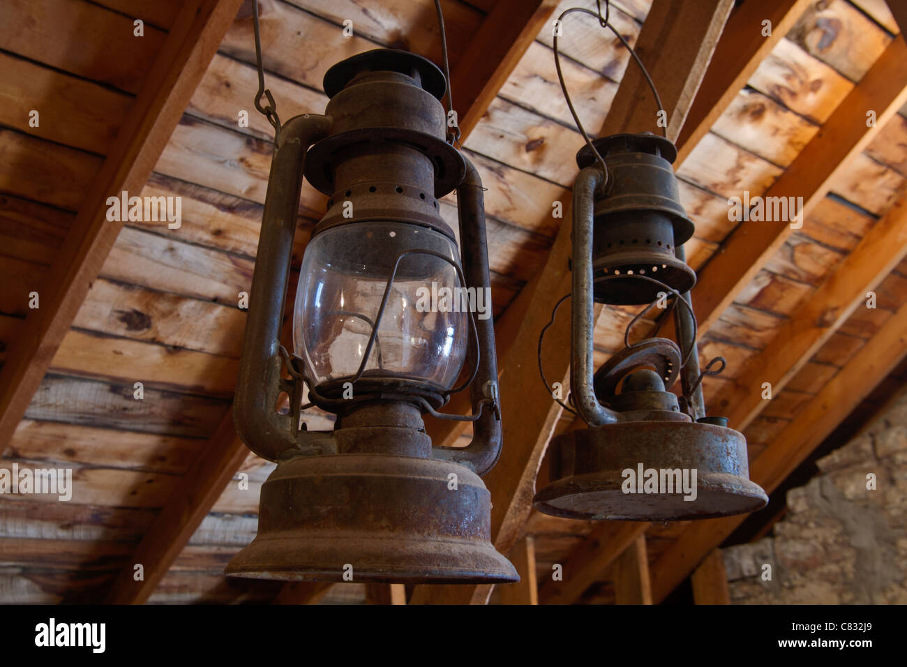 Antique oil lanterns hanging in a barn - Stock Image