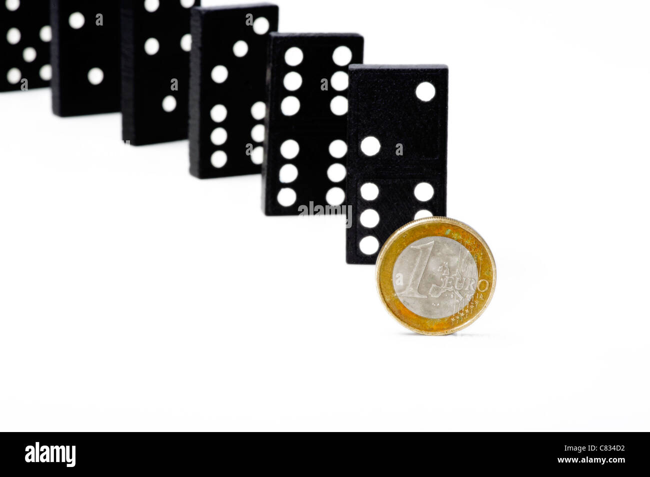 A standing  soiled Euro coin in front of Domino tiles - Stock Image