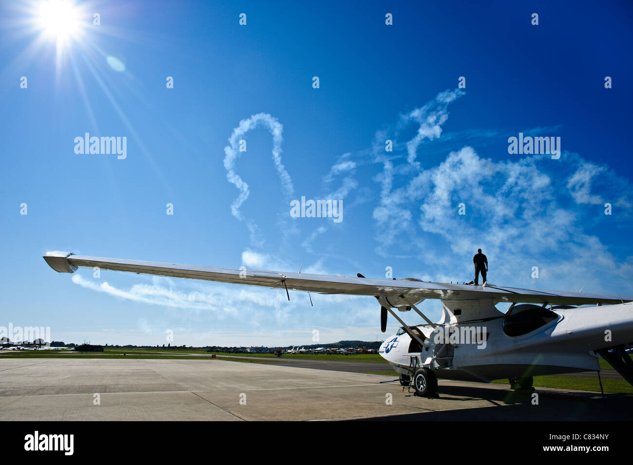 20/08/2010. Shoreham, Uk. Silhouette of the pilot against a bright sun as he walks along the wing of a Catalina - Stock Image