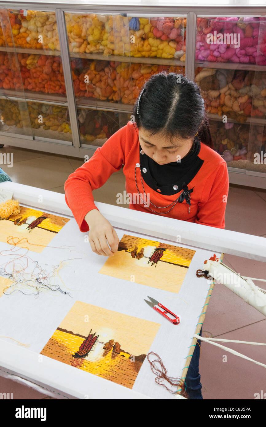 Vietnam, Halong Bay, Halong City, Girls Making Needlework Picture - Stock Image