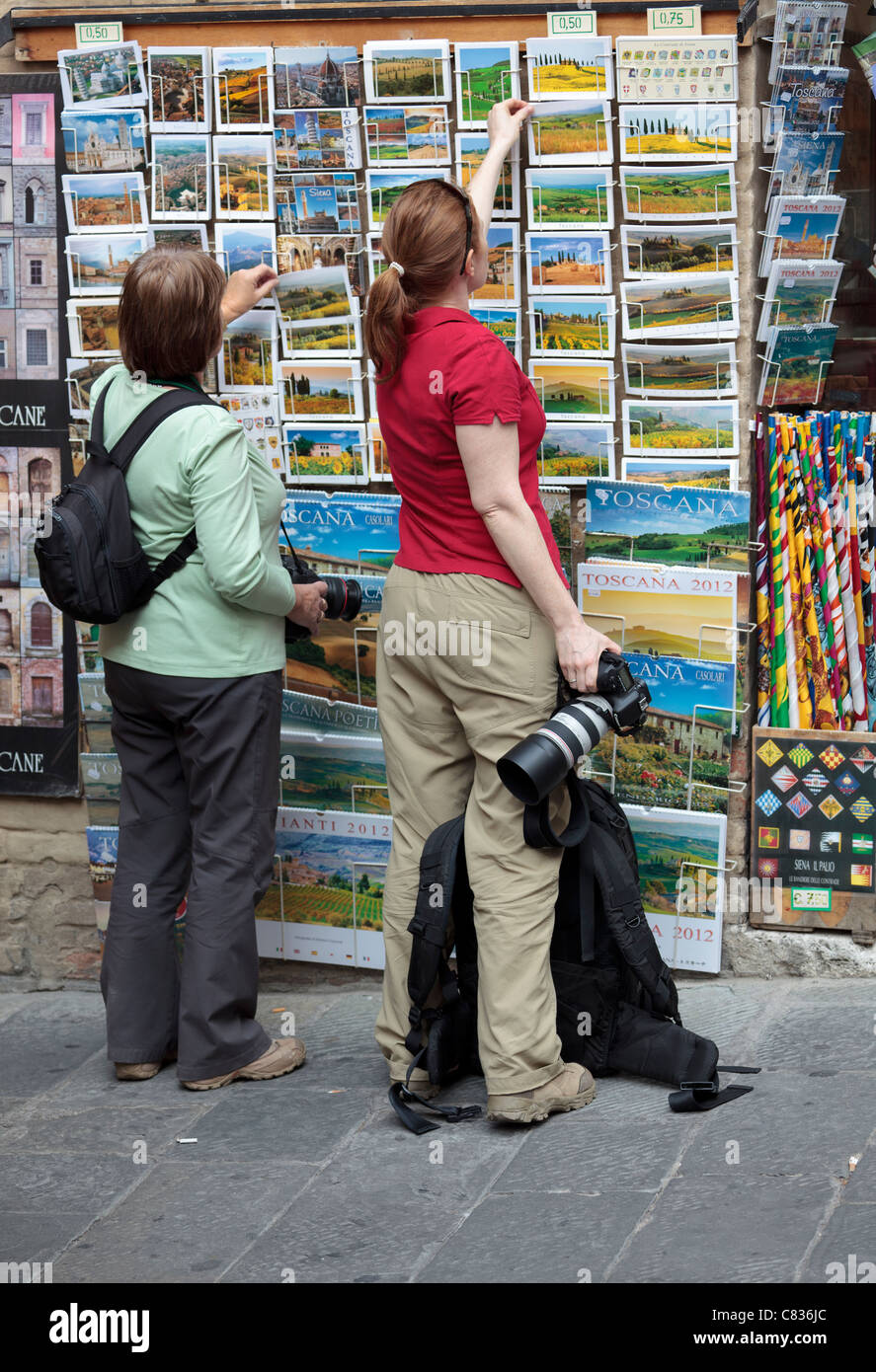 Visitors to Sienna looking at Tuscany postcards on a rack. - Stock Image