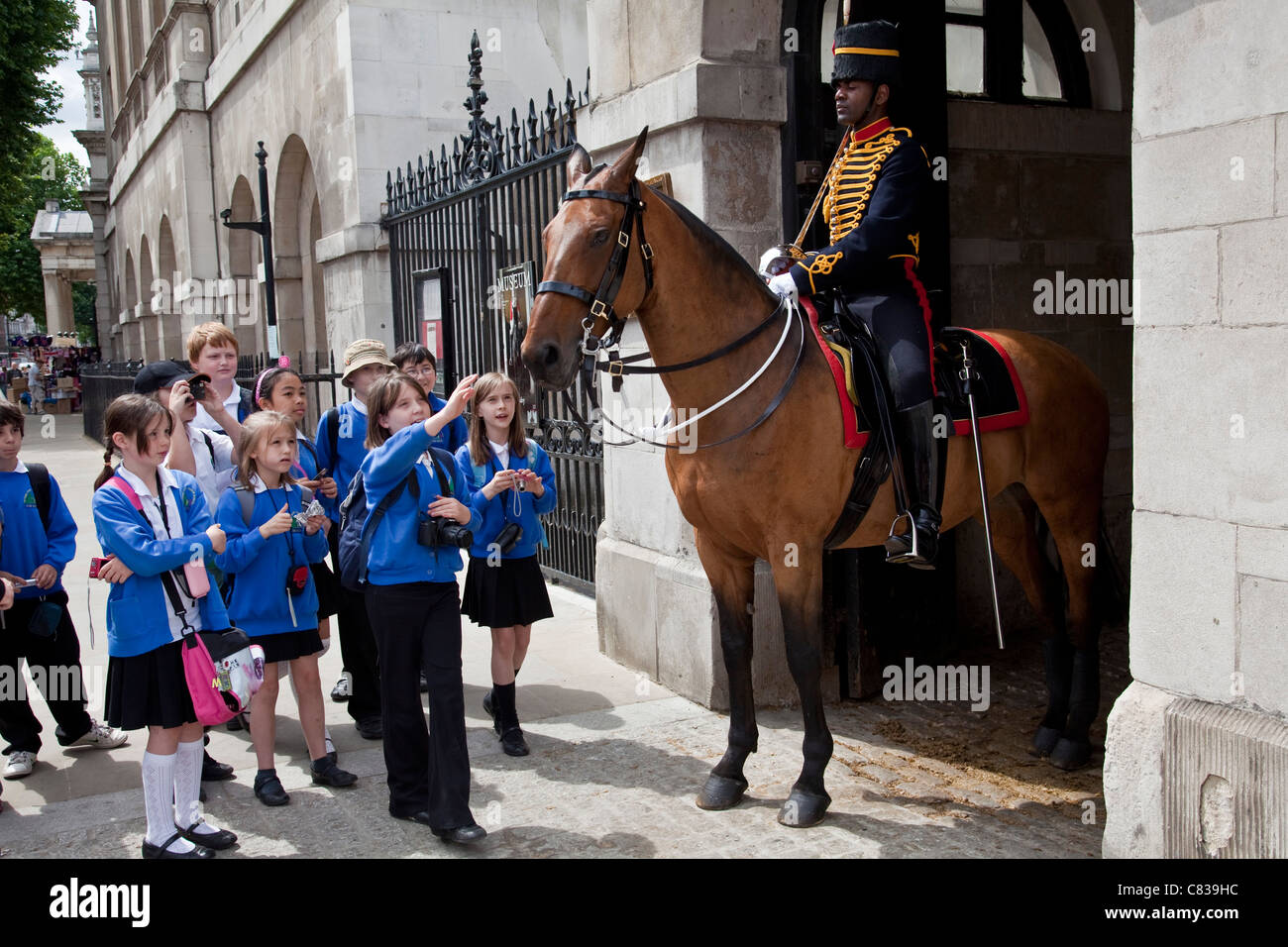 British Schoolchildren pose for photographs with a soldier from the Queen's Life Guard, London, England - Stock Image