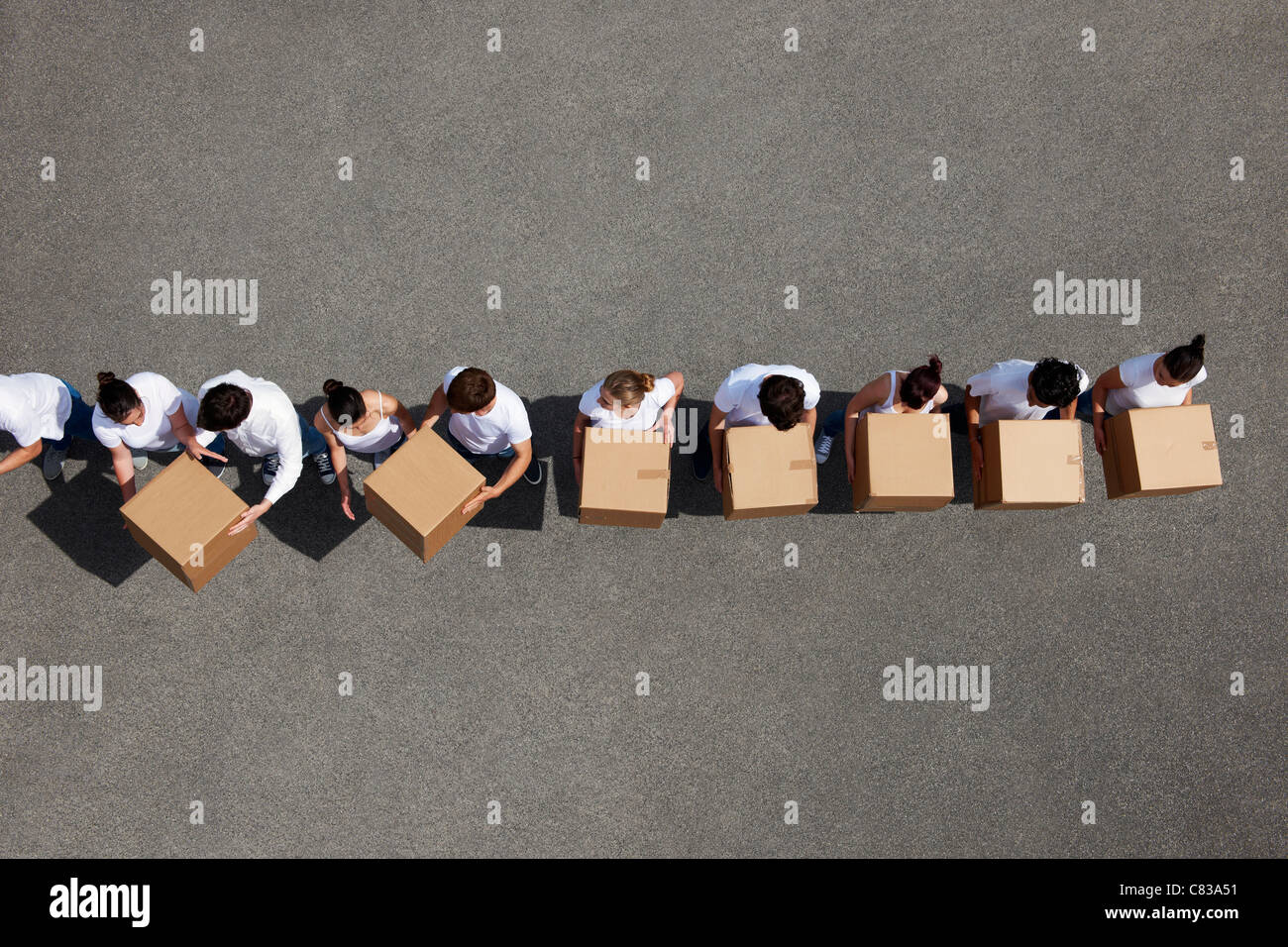 People passing cardboard boxes - Stock Image
