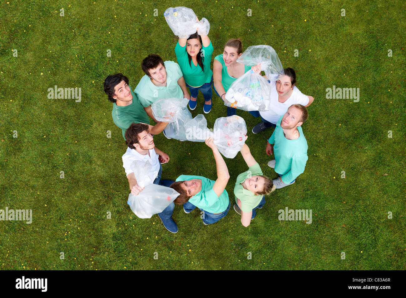 People holding garbage bags on grass - Stock Image