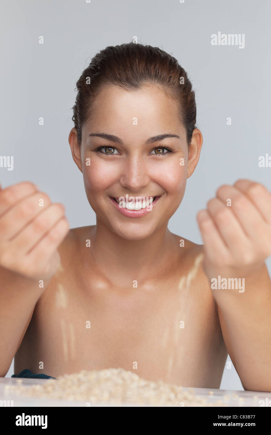 Smiling woman playing with grains - Stock Image
