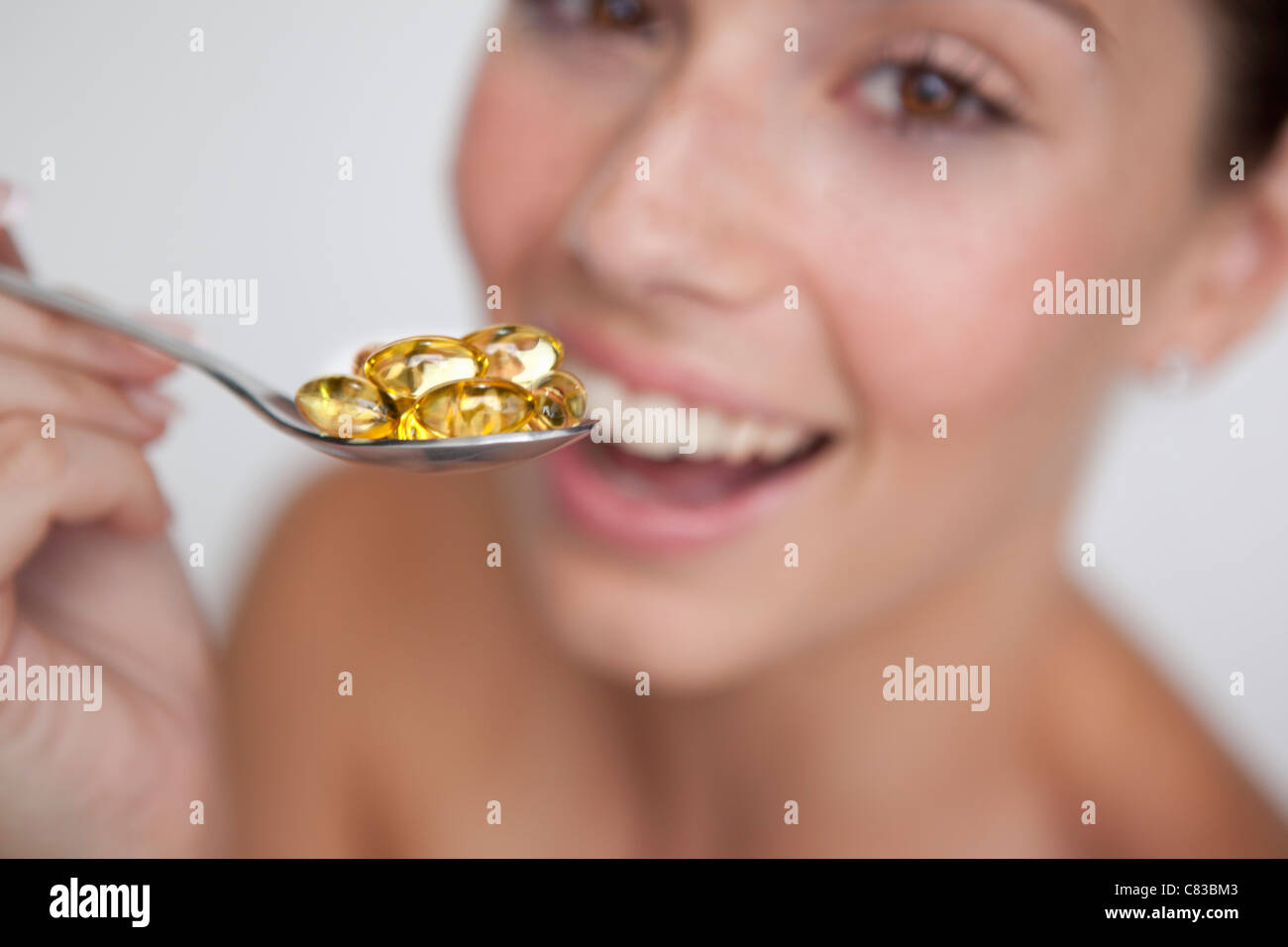 Woman eating spoonful of supplements - Stock Image