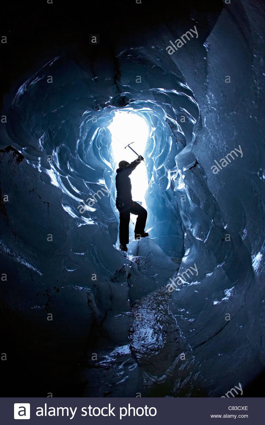 Man exploring glacial cave - Stock Image