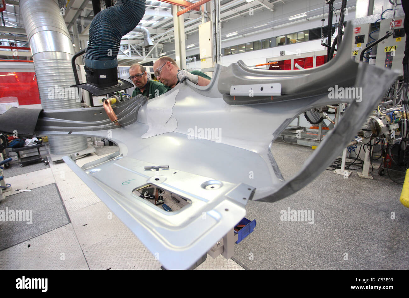 Employees work on a Bentley motor car at the company's factory in Crewe, U.K. - Stock Image