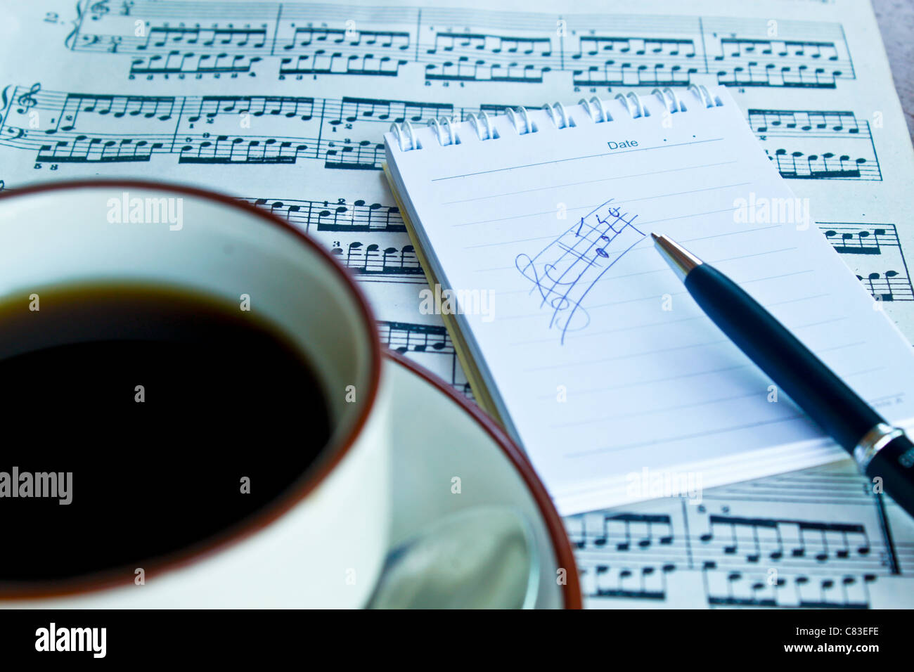 Cafee in cup on background music note and score note with black pen. - Stock Image