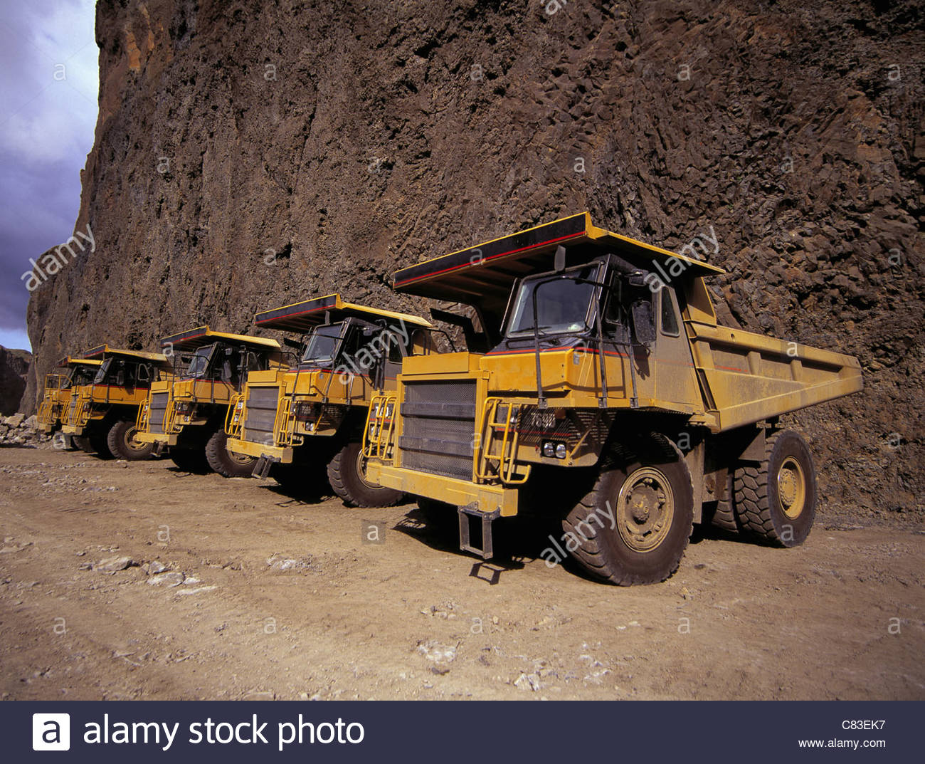Dump trucks parked at quarry - Stock Image
