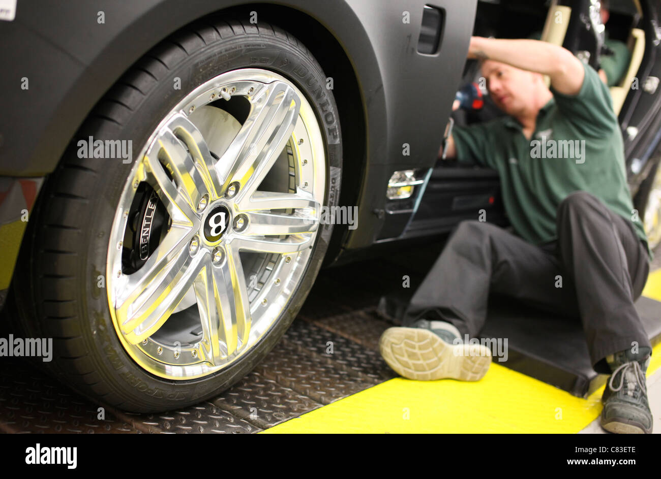 An employee works on a Bentley motor car at the company's factory in Crewe, U.K. - Stock Image