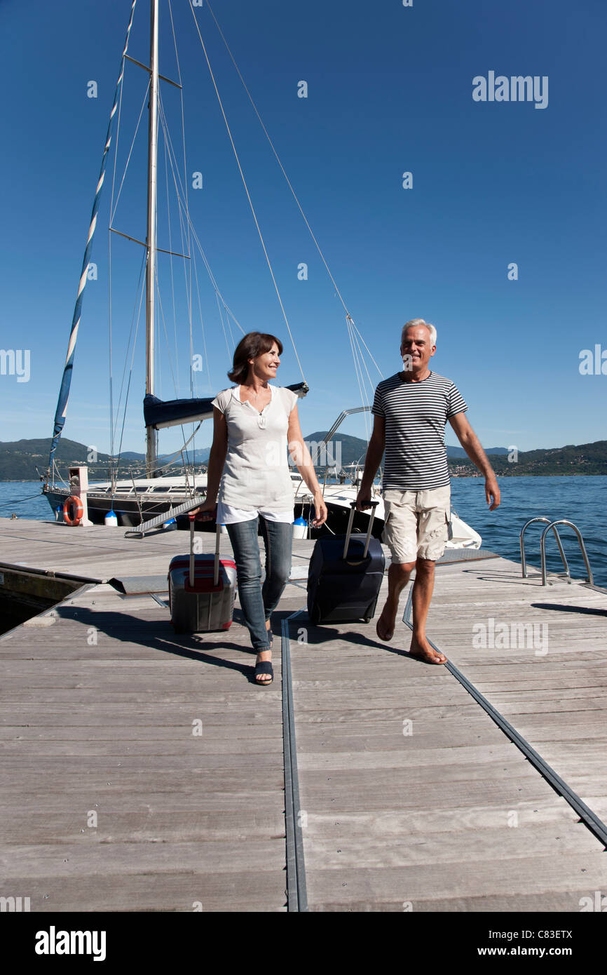 Older couple rolling luggage on pier - Stock Photo