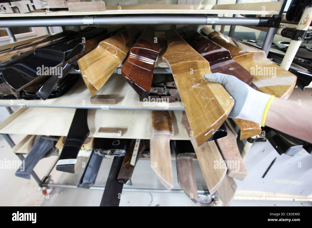 An employee takes a wooden interior piece for a Bentley motor car at the company's factory in Crewe, U.K. - Stock Image