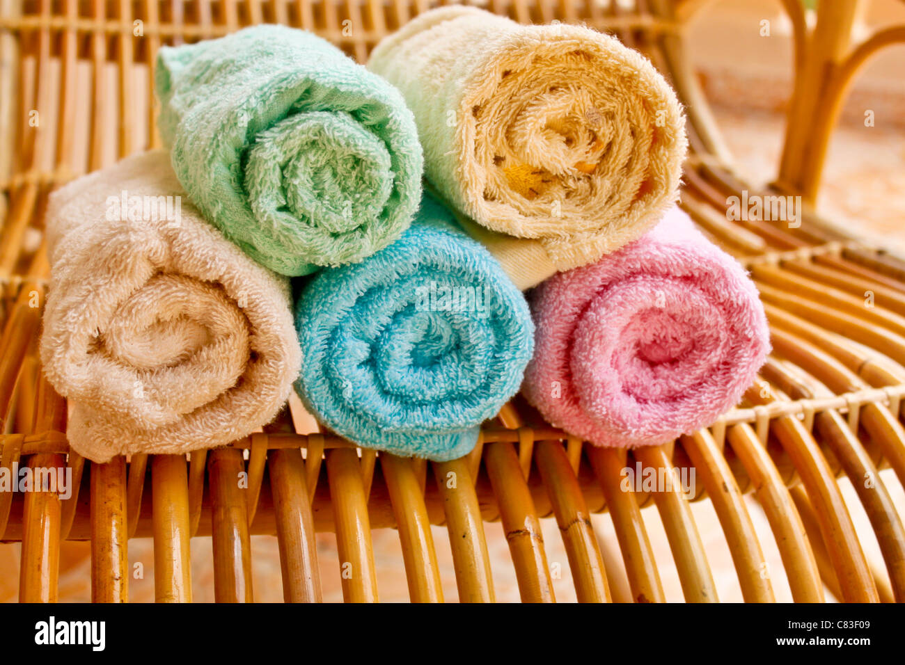 Multicolour towels rolls on wood chair - Stock Image