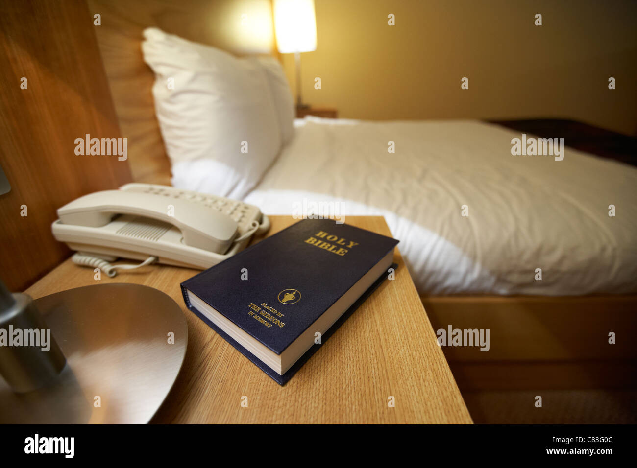 holy bible placed by the gideons on the beside table in the interior of a 4 star hotel bedroom - Stock Image