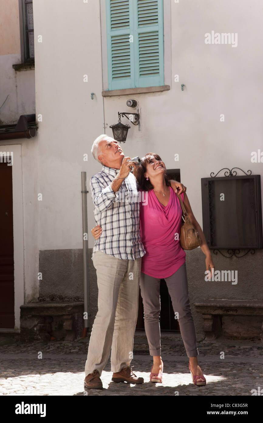 Older couple taking photos in village - Stock Image