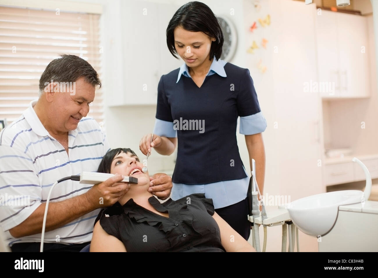 Dentist and assistant working on woman - Stock Image