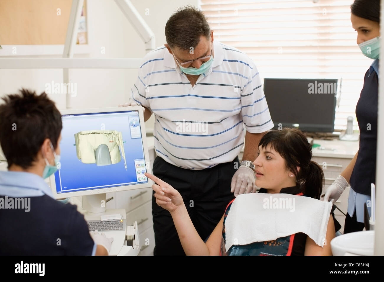 Woman examining model with dentist - Stock Image