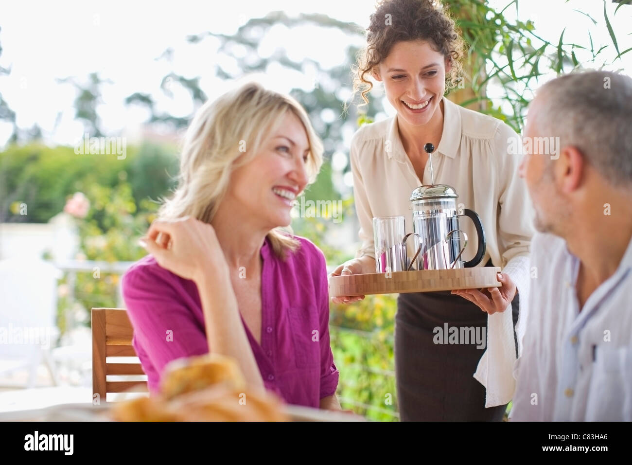 Waitress serving coffee to couple - Stock Image