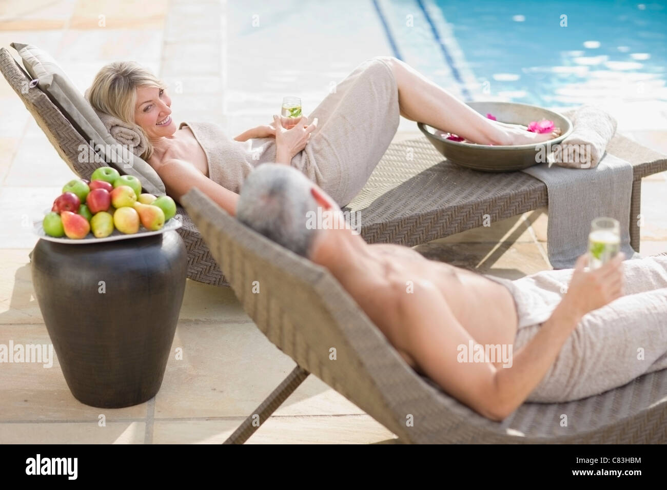 Couple relaxing in lawn chairs by pool Stock Photo