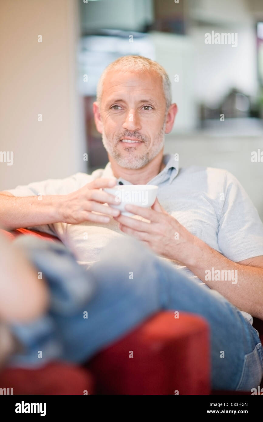 Man drinking coffee in armchair - Stock Image
