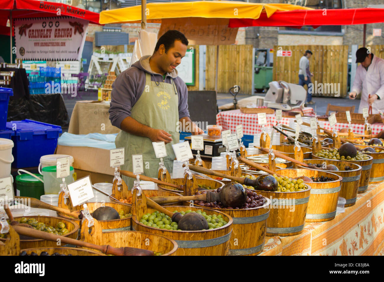Market trader at a olive stall at Borough Market. - Stock Image