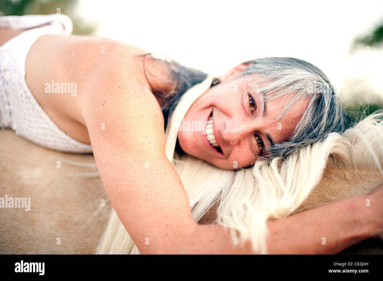 Close up portrait of a woman laying her head on a horses neck. - Stock Image