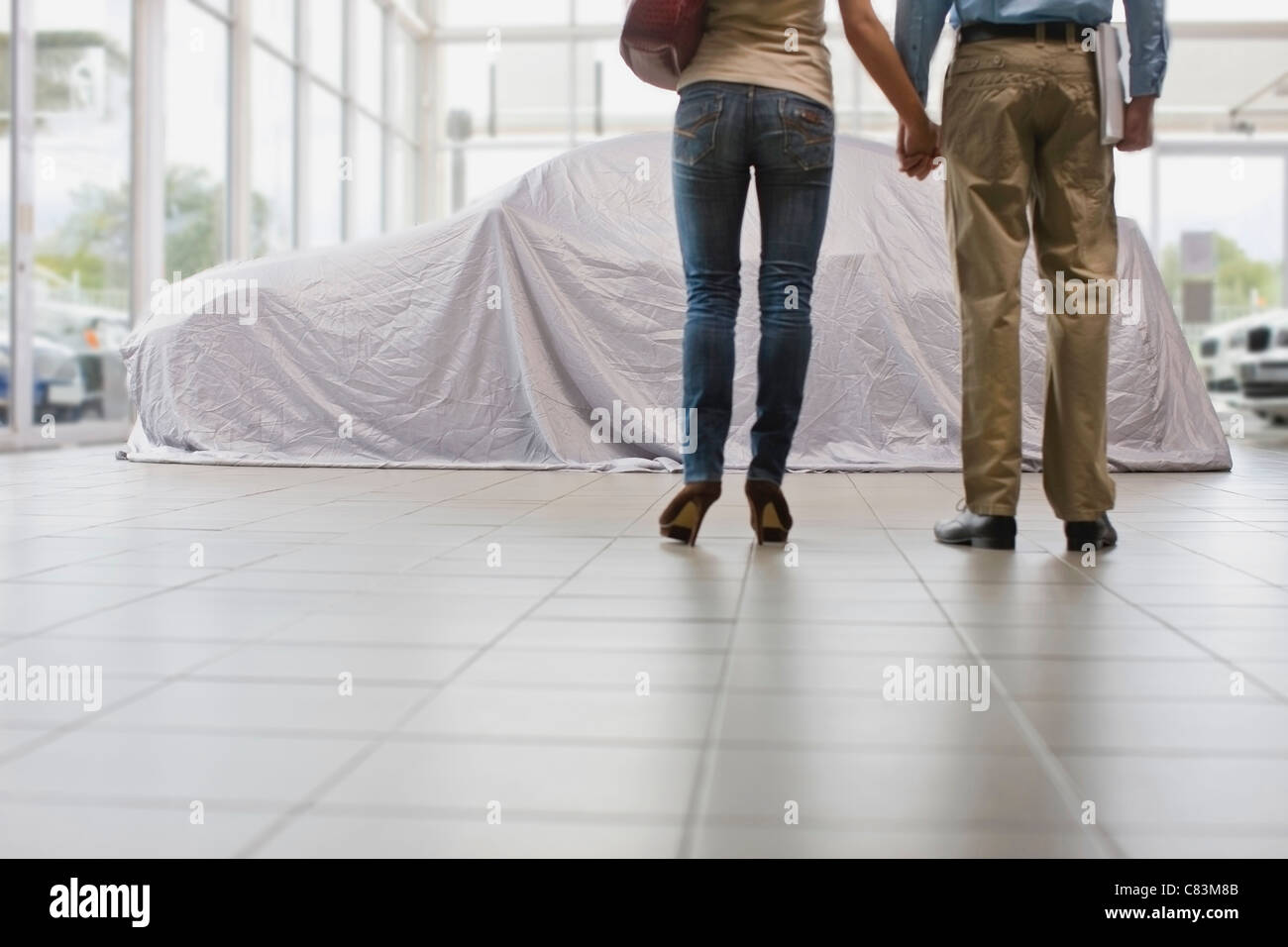 Couple admiring new car under cloth - Stock Image