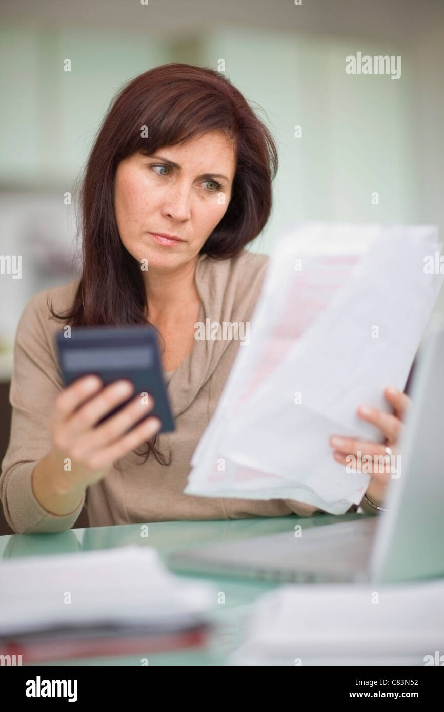 Woman paying her bills at home - Stock Image
