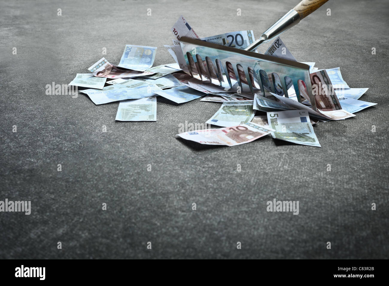 Rake collecting Euro notes - Stock Image