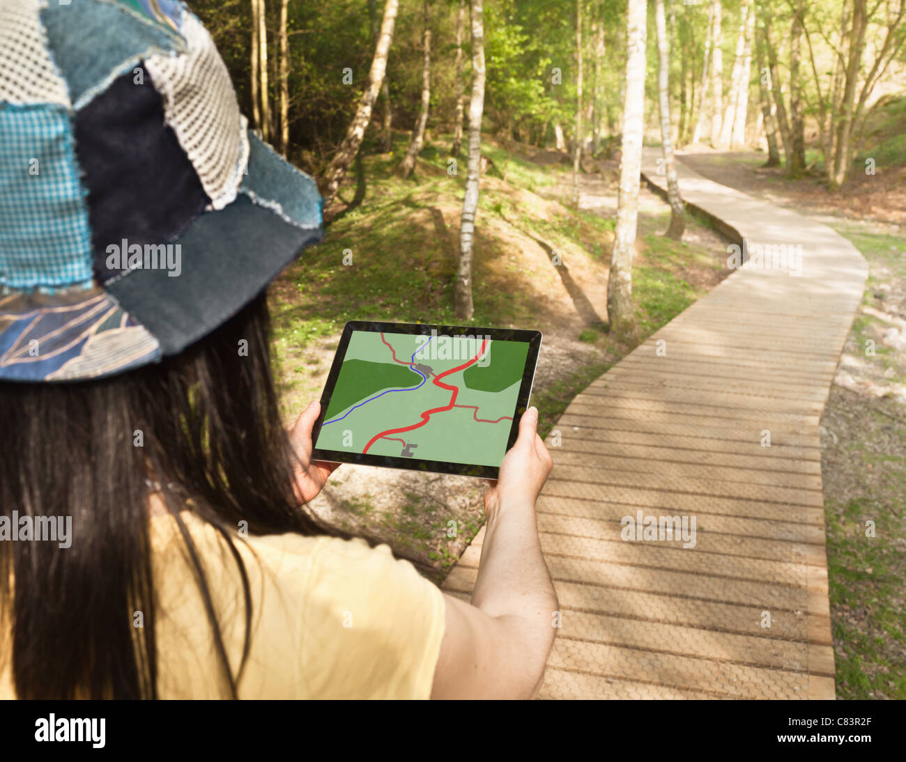 Woman using tablet computer while hiking - Stock Image