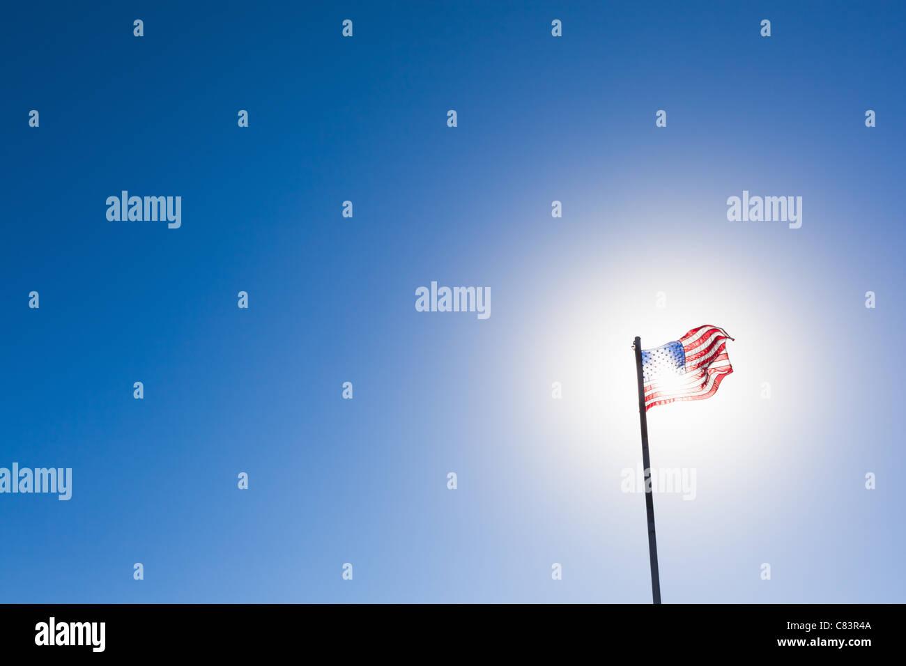 American flag against sun and blue sky Stock Photo