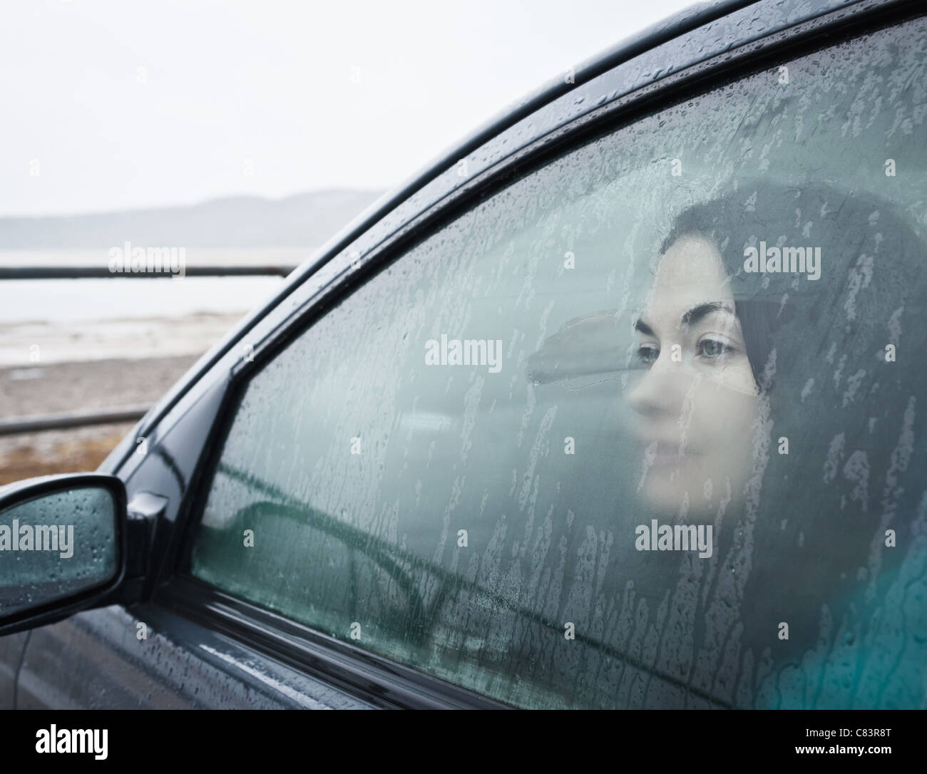 Teenage girl looking out wet car window - Stock Image