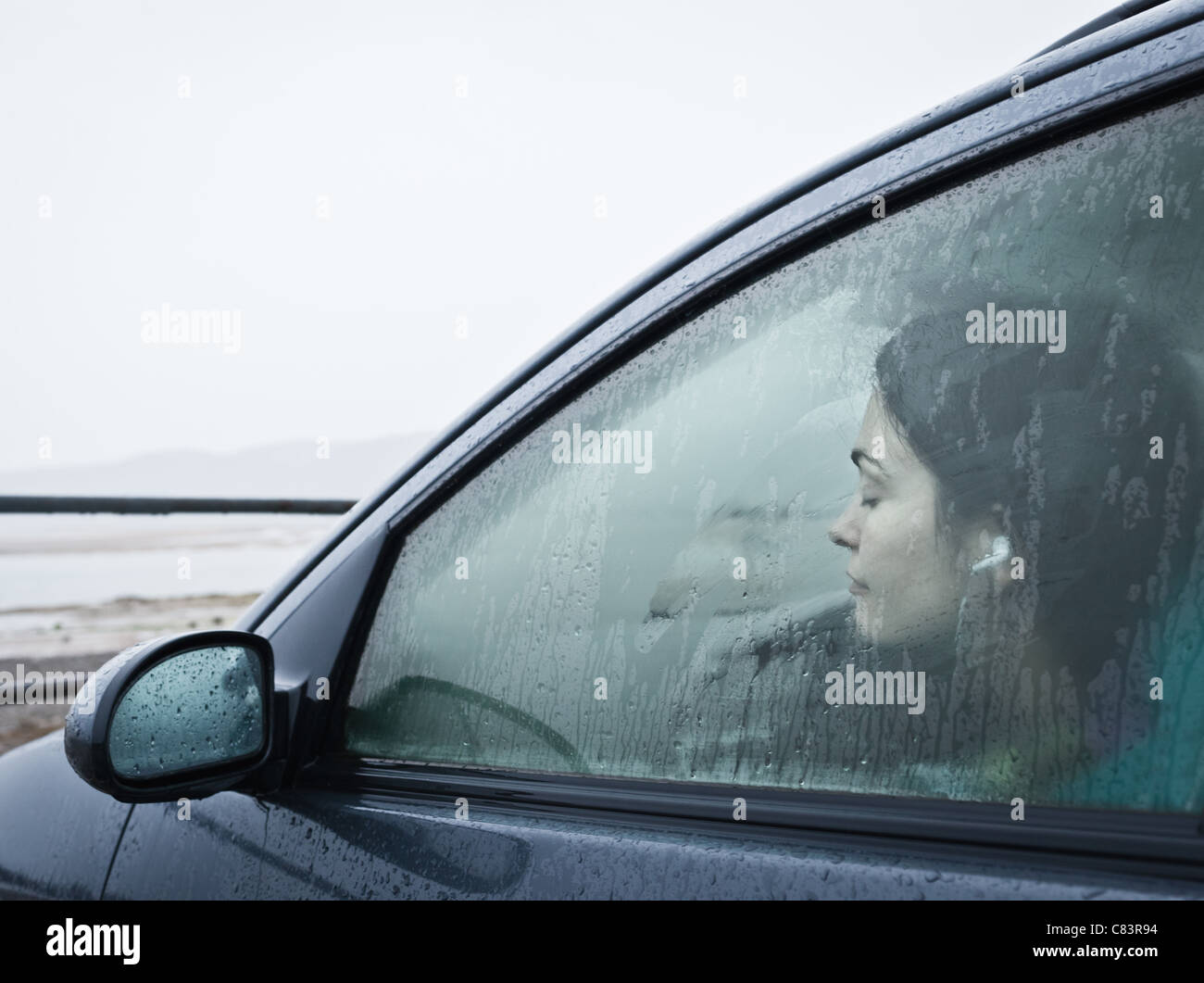 Teenage girl sitting in car by beach Stock Photo