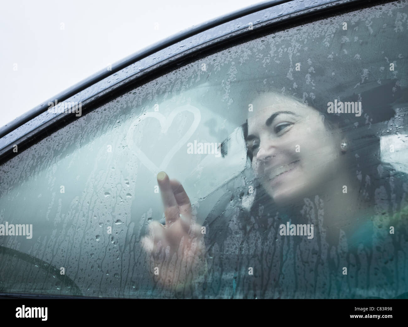 Teenage girl drawing on wet car window Stock Photo