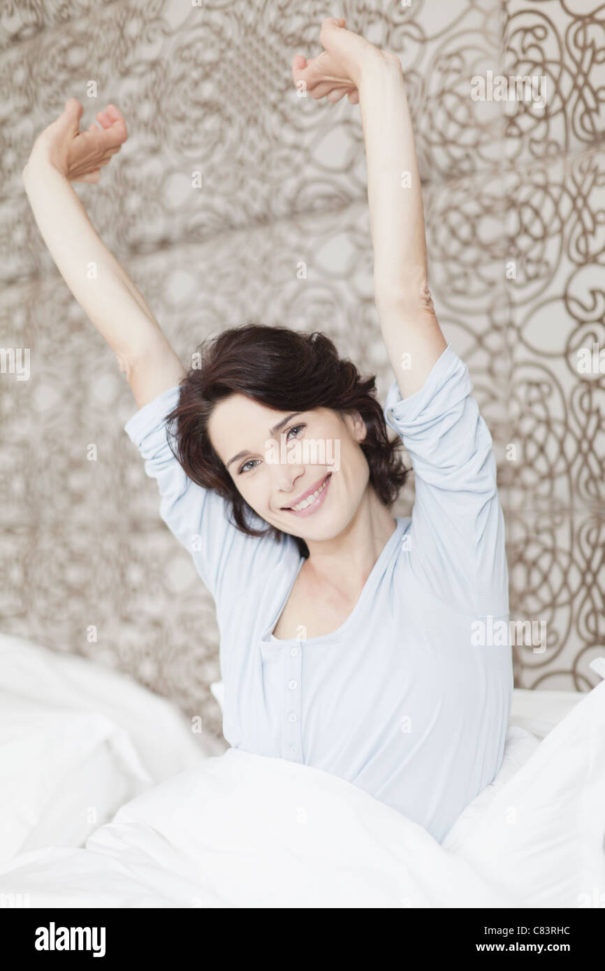 Smiling woman stretching in bed - Stock Image