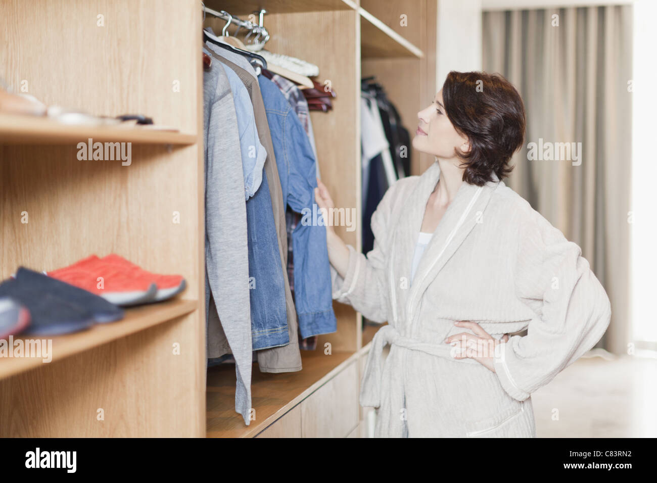 Woman picking clothes out of closet - Stock Image