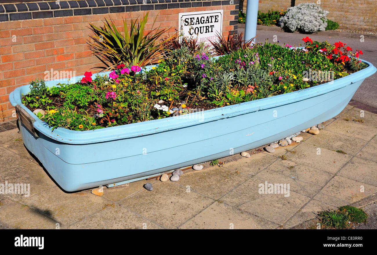 Disused  dinghy turned into  a decorative floral display  and piece of street furniture  at East Wittering  seaside - Stock Image