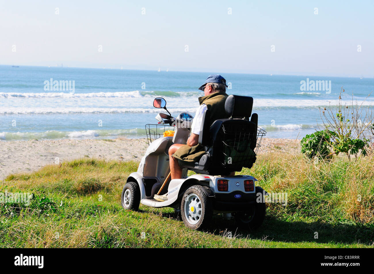Disabled man in mobility chair  looking out  to the Solent on the Greensward  West Wittering Beach, near Chichester. - Stock Image